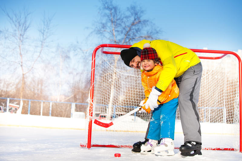 Dad teach little boy son to play ice hockey. Father teach son to play ice hockey and hold hockey stick standing near gates on ice royalty free stock image