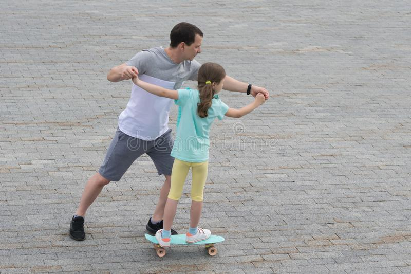 Dad teaches daughter to skateboard in a city park stock photo