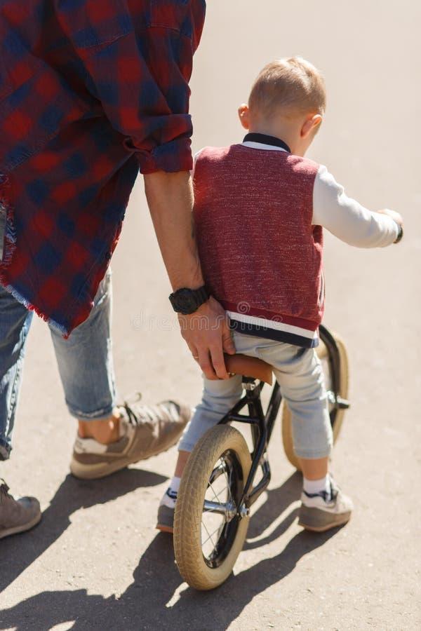Dad teaches son to ride stock photos