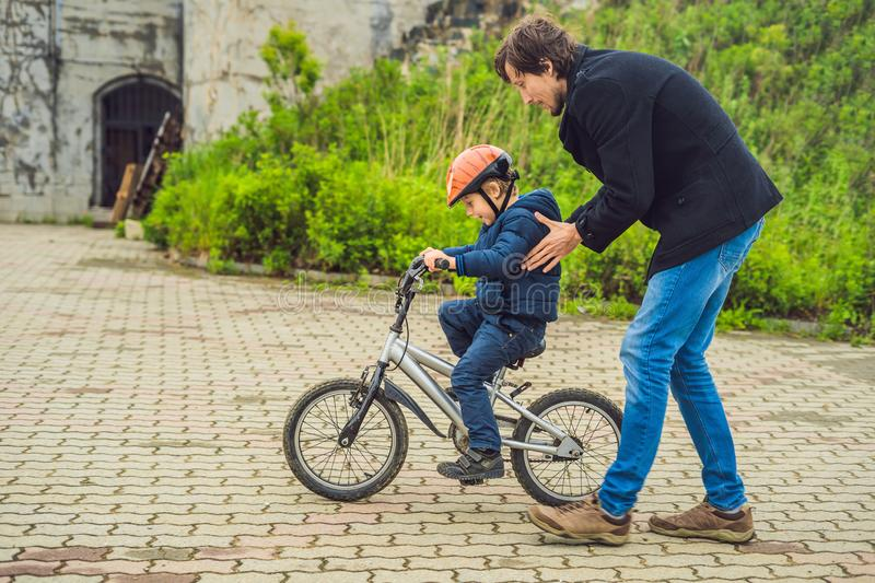 Dad teaches son to ride a bike in the park royalty free stock photography
