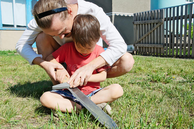 Dad teaching boy in machete sharpening stock images