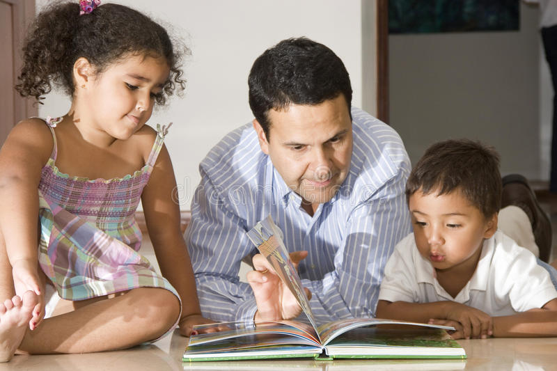 Dad teaching children. Portrait of family, dad teaching his children at home stock photography