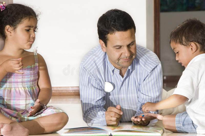 Dad teaching children. Portrait of family, dad teaching his children at home stock photo