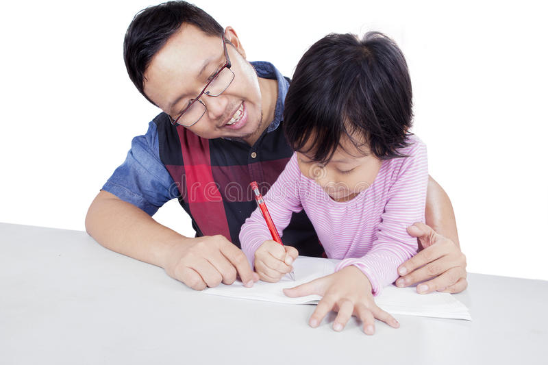 Dad teaching his daughter to study. Young dad teaching his daughter to study and doing homework, isolated on white background stock photography