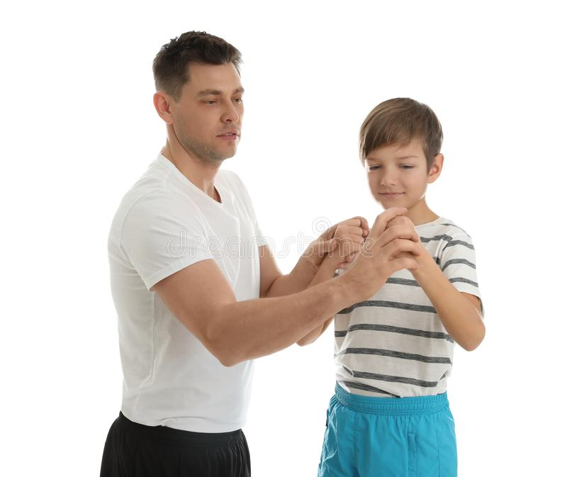 Dad teaching his son to fight isolated. On white stock photo