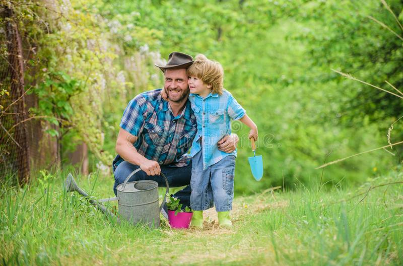 Dad teaching little son care plants. Little helper in garden. Planting flowers. Growing plants. Fresh seedlings. Take. Care of plants. Boy and father in nature royalty free stock photo