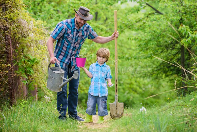 Dad teaching little son care plants. Little helper in garden. Make planet greener. Growing plants. Take care of plants. Day of earth. Boy and father in nature royalty free stock photos