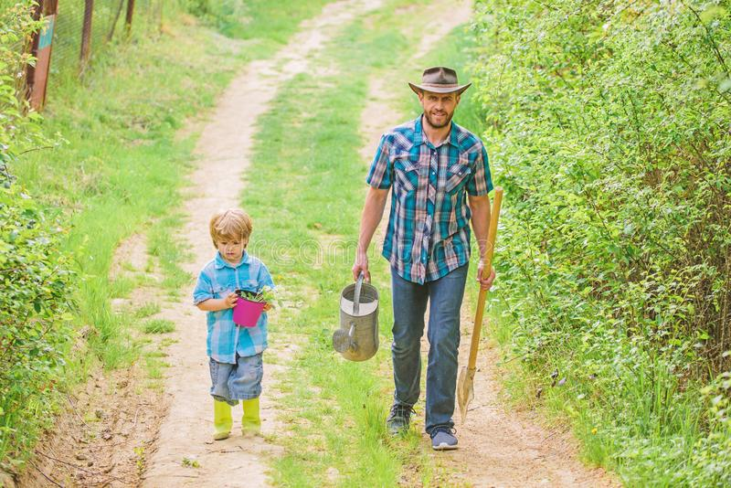 Dad teaching son care plants. Arbor day. Planting trees. Tree planting tradition. Little helper in garden. Planting. Flowers. Growing plants. Boy and father in royalty free stock photography