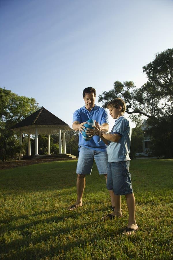 Dad teaching son football. royalty free stock photos