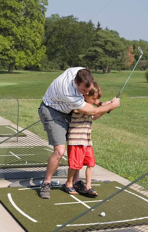 Dad Teaching Son Golf. A Dad Teaching His Son to Golf royalty free stock photography