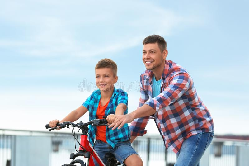 Dad teaching son to ride bicycle. Outdoors stock photo