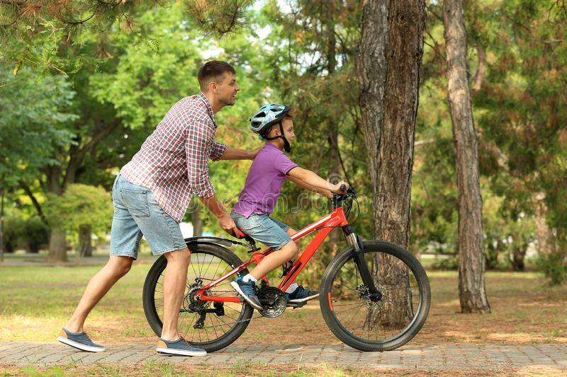 Dad teaching son to ride bicycle. In park royalty free stock photo