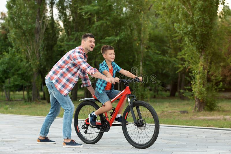 Dad teaching son to ride bicycle. In park stock photo