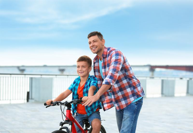 Dad teaching son to ride bicycle. Outdoors royalty free stock photo
