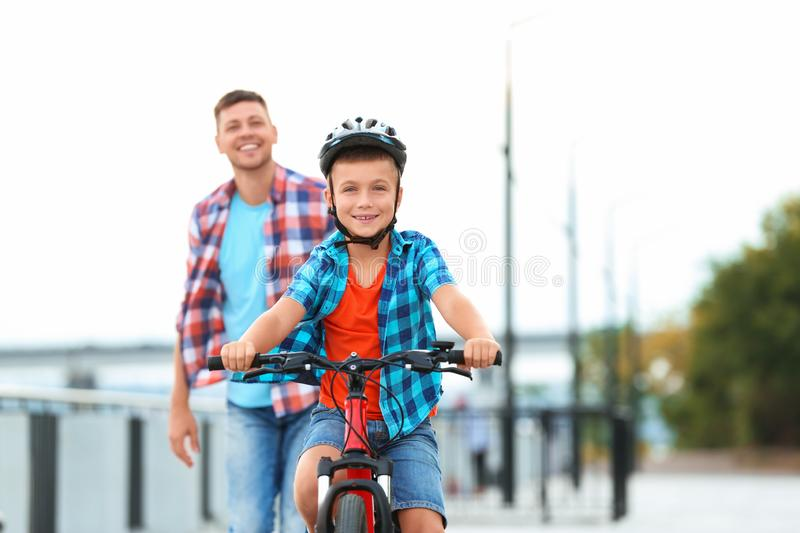 Dad teaching son to ride bicycle. Outdoors stock photos