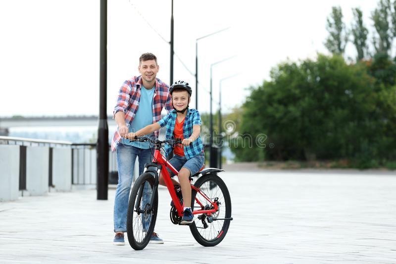 Dad teaching son to ride bicycle. Outdoors royalty free stock photography