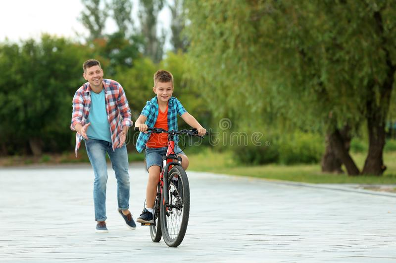 Dad teaching son to ride  in park. Dad teaching son to ride bicycle in park royalty free stock photography