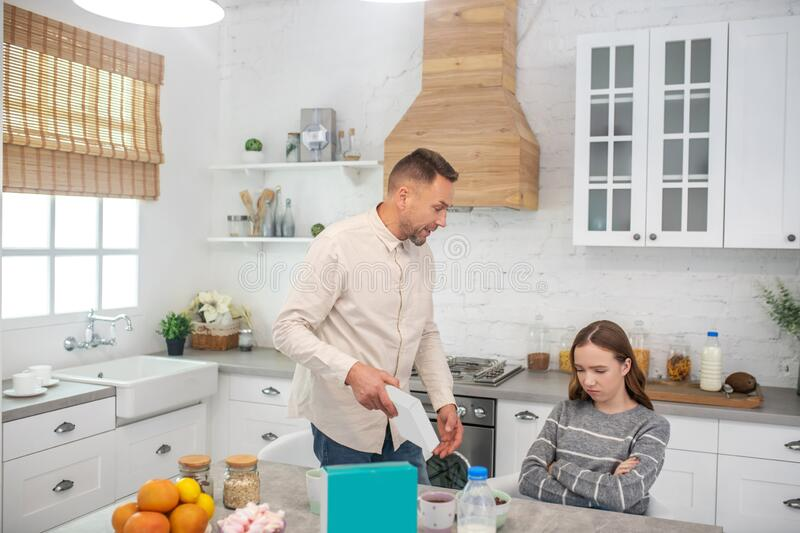Dad telling his daughter about good nutrition in the kitchen. stock image