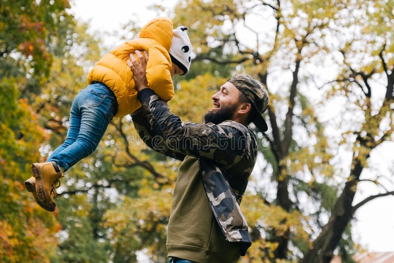 Dad throwing up daughter in the air. Young father having fun with his daughter in the autumn park. Dad throwing up daughter in the air stock photography