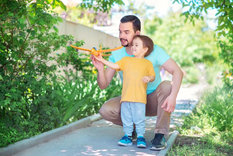Dad and toddler son together launch toy airplane, both man and boy are looking at plane. Father and son spending good time royalty free stock photos