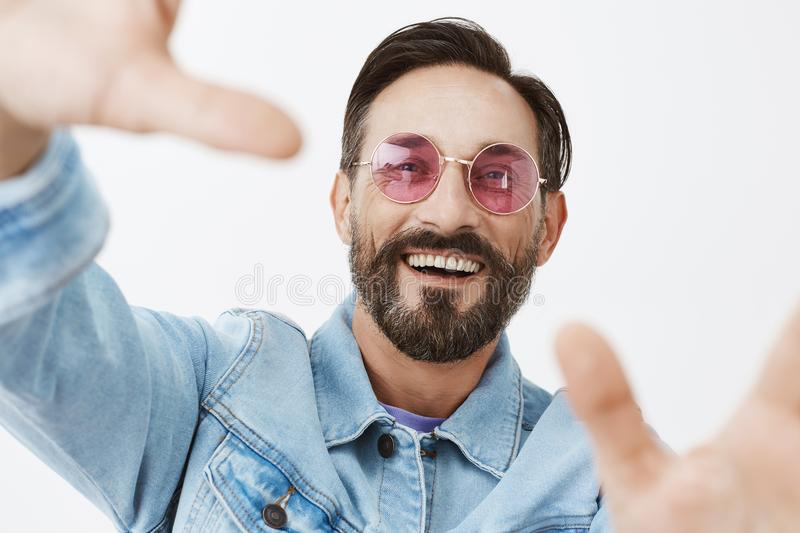 Dad trying make selfie to post it online. Portrait of stylish and happy handsome adult man with thick beard and stylish. Haircut, pulling hands towards camera royalty free stock images