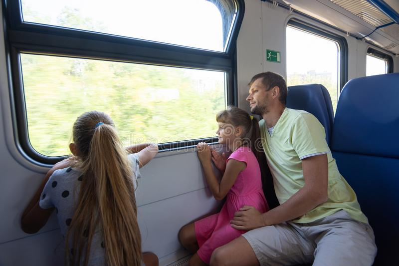 Dad and two daughters in an electric train car, look out the window with enthusiasm royalty free stock photo
