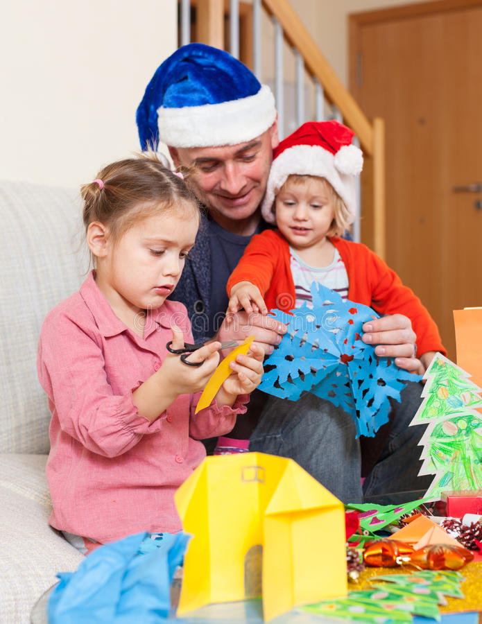 Dad with two daughters making crafts stock photography