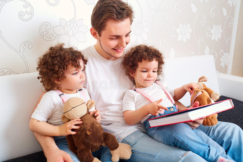 Dad with two daughters twins reading a book on the couch in the stock photography