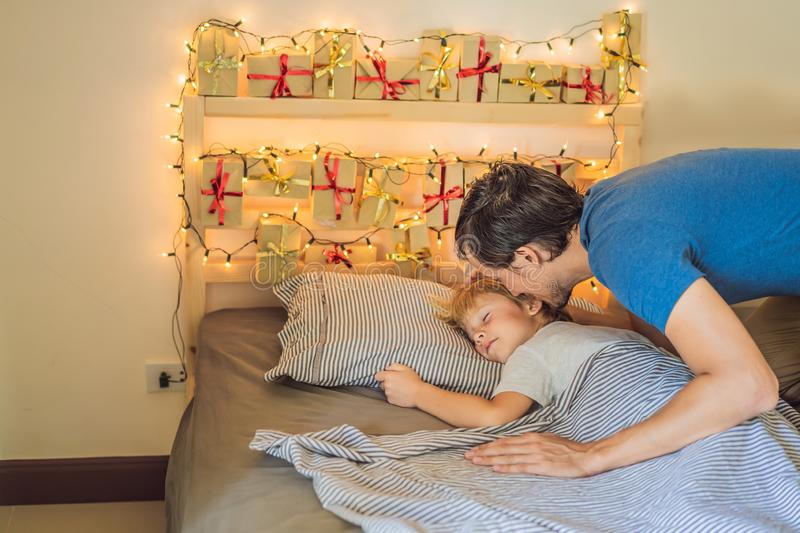 Dad wakes up little boy in the morning and home made advent calendar on a shelf. Winter seasonal tradition. Christmas. Advent calendar stock image