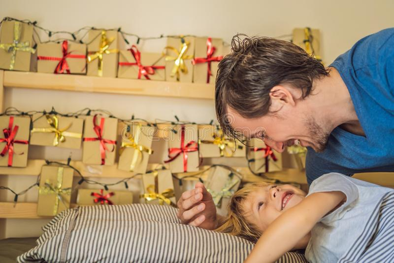 Dad wakes up little boy in the morning and home made advent calendar on a shelf. Winter seasonal tradition. Christmas. Advent calendar stock images