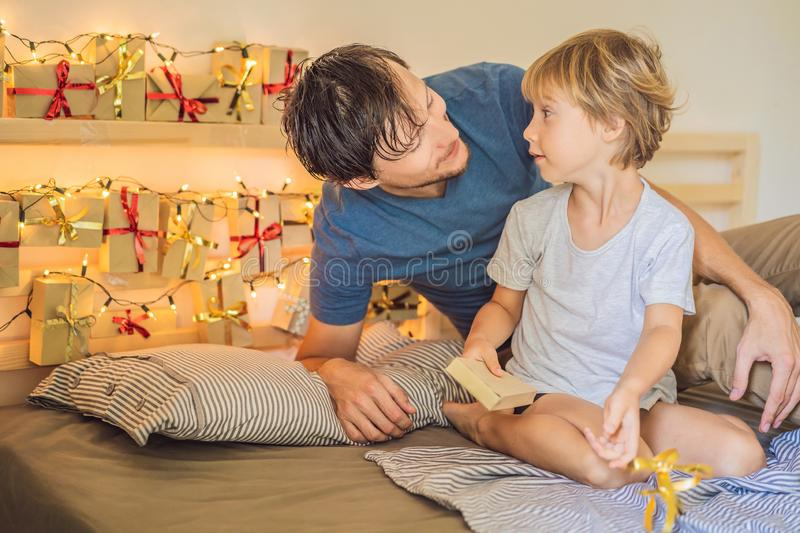 Dad wakes up little boy in the morning and home made advent calendar on a shelf. Winter seasonal tradition. Christmas. Advent calendar royalty free stock image