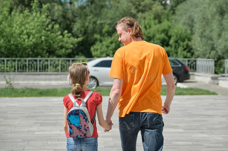 Dad walks with his daughter holding hands. Outdoor, sunny summer day, back view stock photo