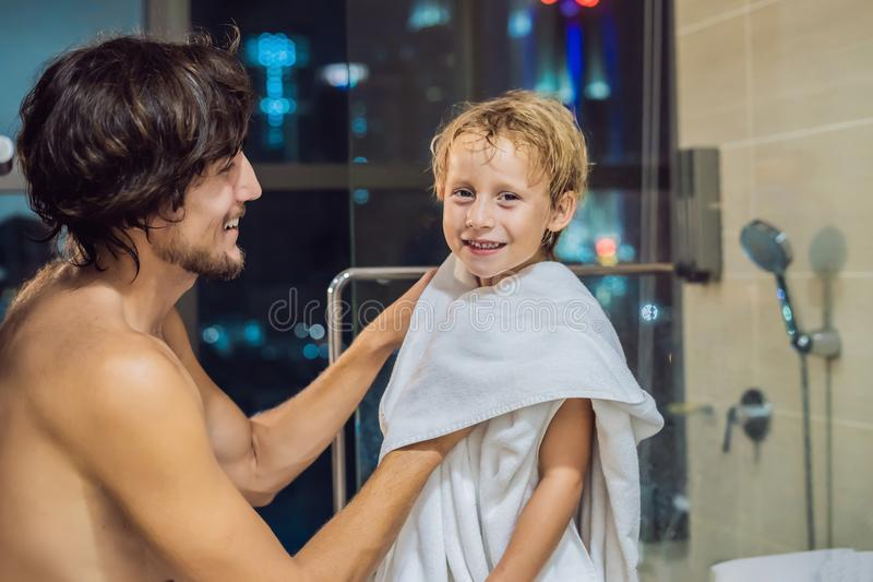Dad wipes his son with a towel after a shower in the evening before going to sleep on the background of a window with a panoramic stock image
