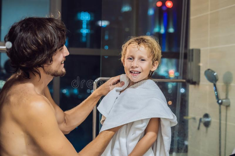 Dad wipes his son with a towel after a shower in the evening before going to sleep on the background of a window with a. Panoramic view of the city stock photography