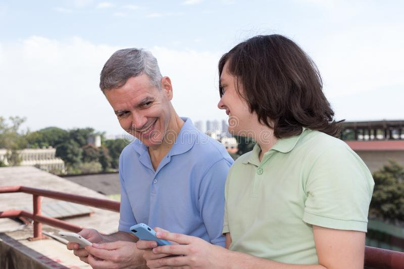 Dad and young adult son. Fathers Day. Male and parent are looking to each other holding mobile phone outside. Concept of family, stock photo