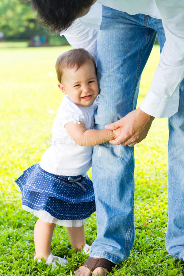 Daddy don't go. Beautiful toddler girl holding daddy's leg don't let him go royalty free stock photos