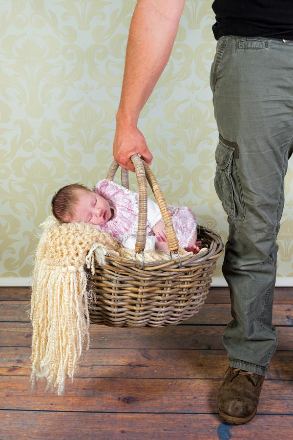 Daddy goes baby shopping. Daddy holding an old wicker shopping basket with his 11 days old newborn baby stock photography