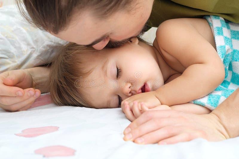 Daddy kissing sleeping baby daughter stock image