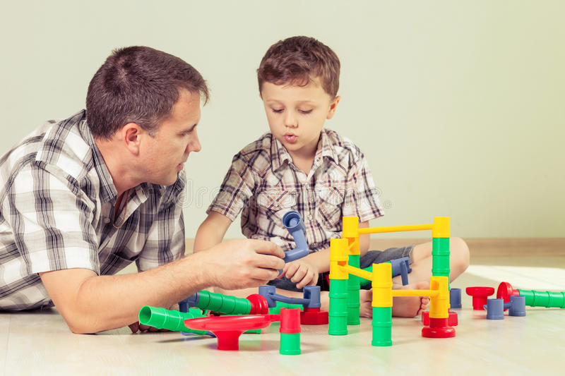 Daddy with little boy playing with toy on the floor at the day. Time. Concept of friendly family royalty free stock photo