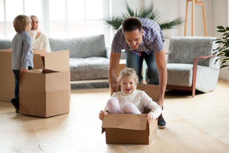 Daddy playing with daughter riding in box on moving day. Concept, little excited girl enjoying game with father in living room, happy family kids having fun in royalty free stock photography