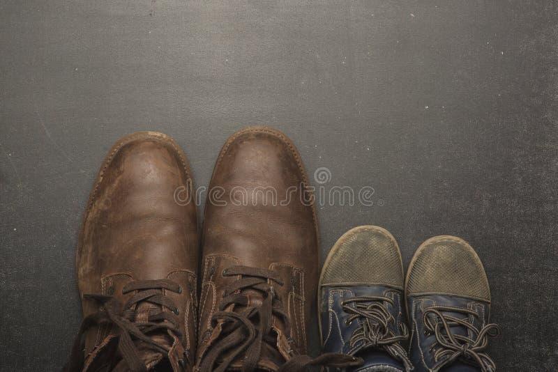 Daddy& x27; s起动和baby& x27; s鞋子,父亲节概念 免版税库存图片