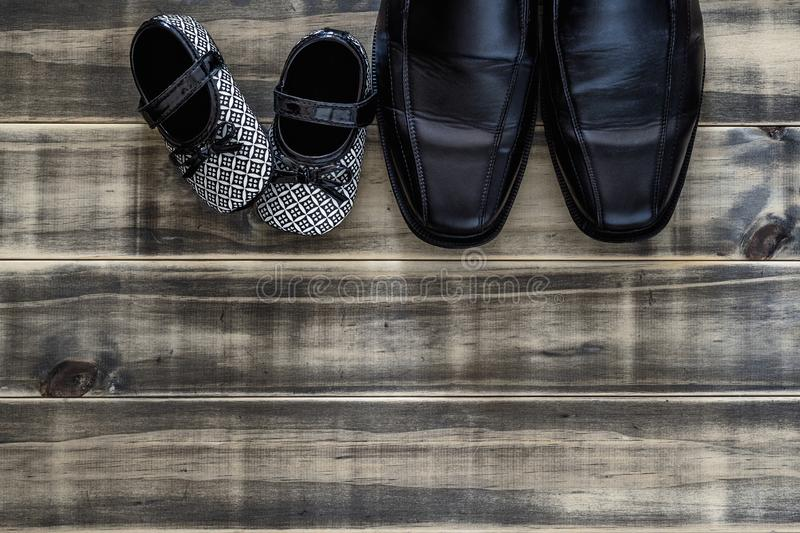 Daddy`s black business shoes and black and white kids sneakers side by side on grunge rusty wood, concept of family, single paren. T and father`s day, Top view royalty free stock image