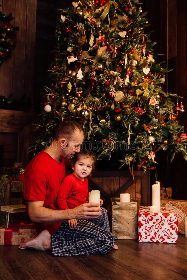 Daddy`s daughter blowing out candles at a Christmas tree. They sit on the floor wearing red T-shirts and pajamas. Family values royalty free stock photography