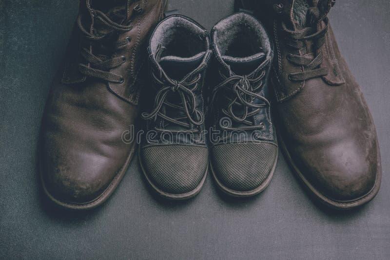 Daddy& x27; s laarzen en baby& x27; s schoenen, het concept van de vadersdag stock foto