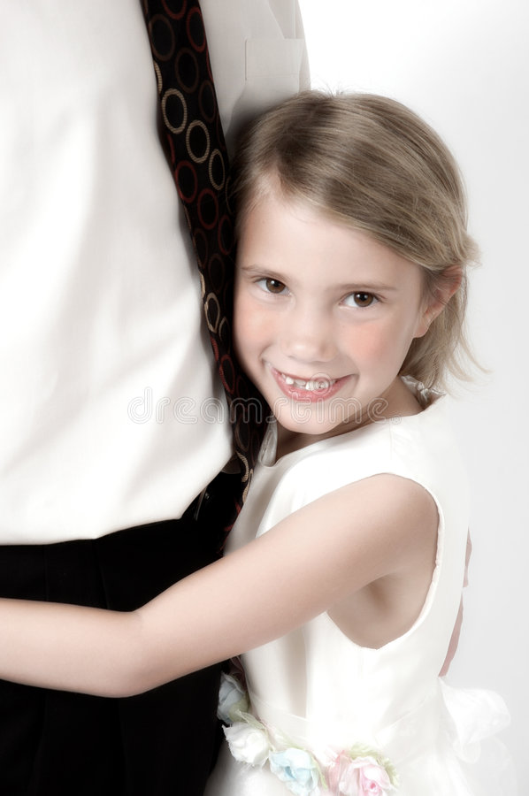 Daddy's little Girl. Little girl hugs her daddy. Dad is standing next to her in white shirt and tie. Little girl hugs her dad at his waist line. Image has been royalty free stock images
