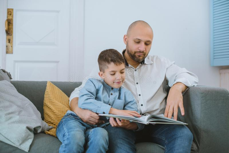 Daddy with son relaxing with the book on sofa. royalty free stock images