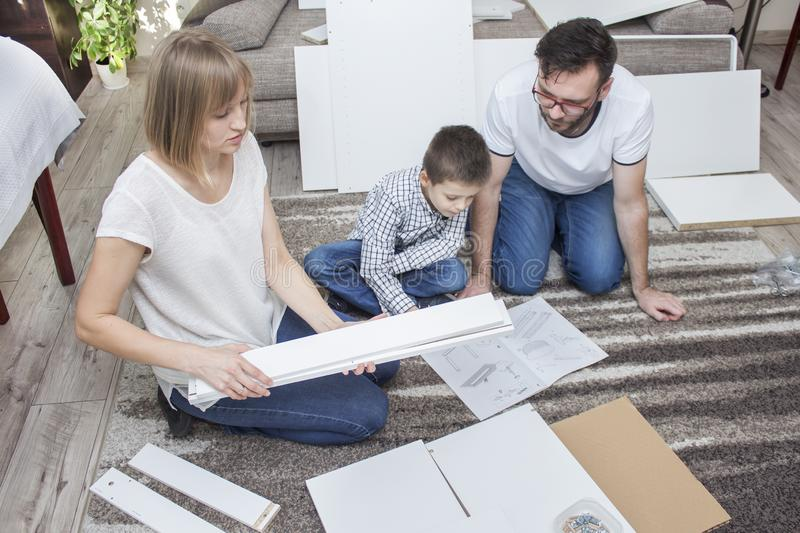 Daddy and son spend their free time rolling furniture together. Mom keeps white long elements in her hands royalty free stock image