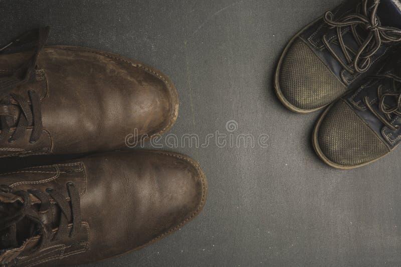 Daddy& x27; stivali di s e baby& x27; scarpe di s, concetto di giorno di padri fotografia stock libera da diritti