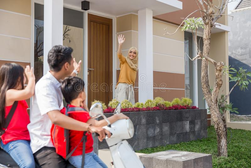 Daddy taking his kids to school by motor bike. Portrait of daddy taking his kids to school by motor bike waving goodbye to mommy royalty free stock photo