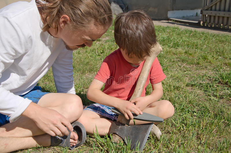 Daddy teaching boy in ax sharpening royalty free stock photos